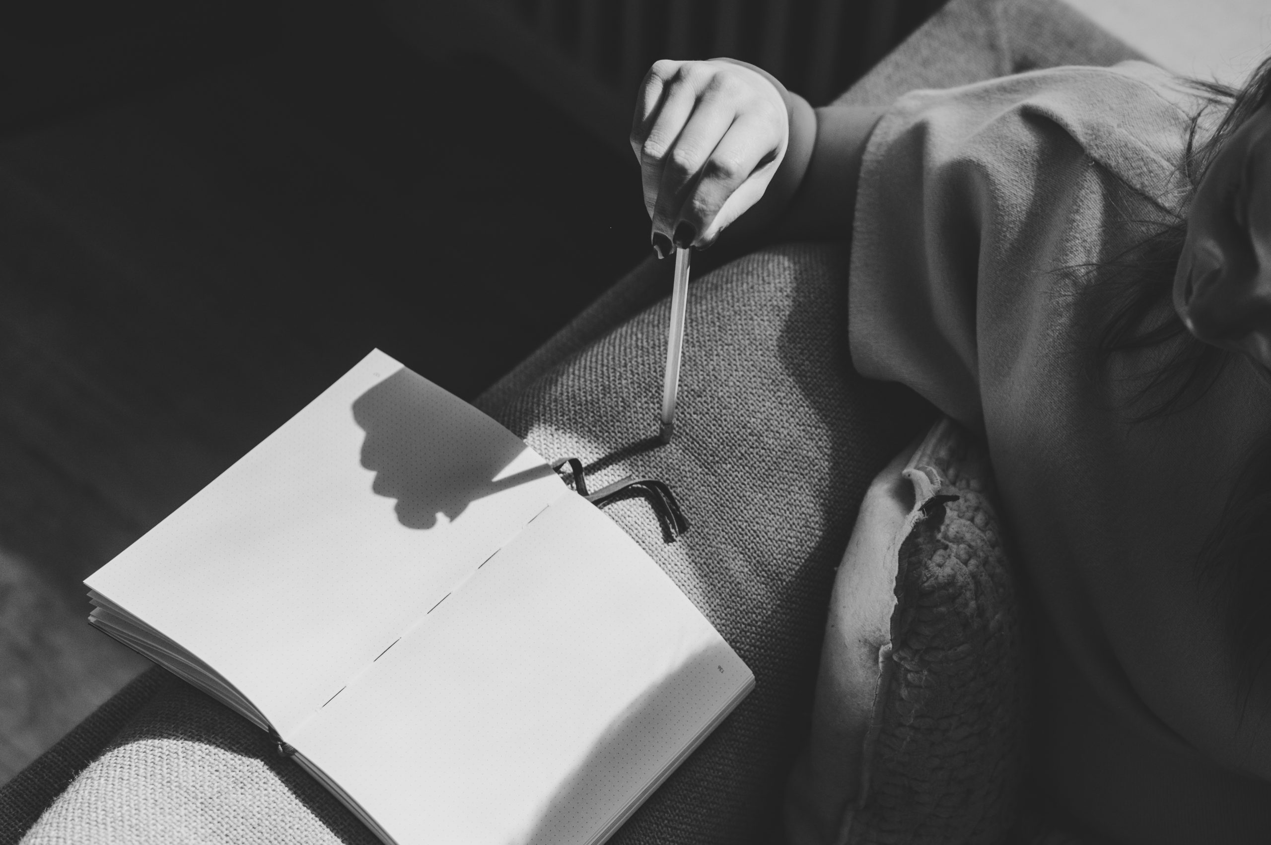 woman sitting in couch writing in notebook